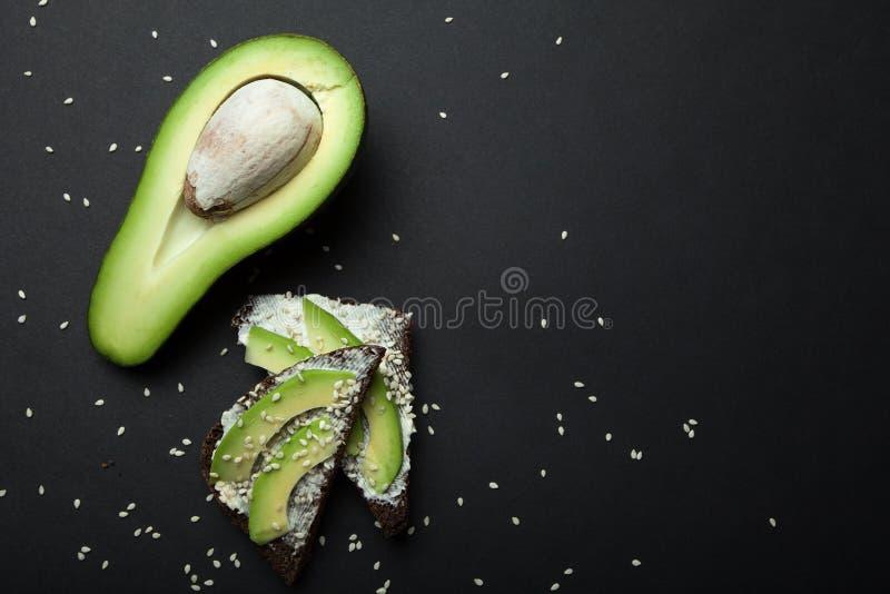 Schwarzes Roggenbrot mit geschnittener Avocado, einem einfachen und heilenden rustikalen Sandwich Raum f?r Text stockbilder