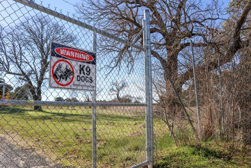 Schwarzes, Roten und weißen warnenden Hunde K9, kommen mit Vorsichtwarnschild auf Hochseiltor und Grenzzaun herein lizenzfreie stockbilder