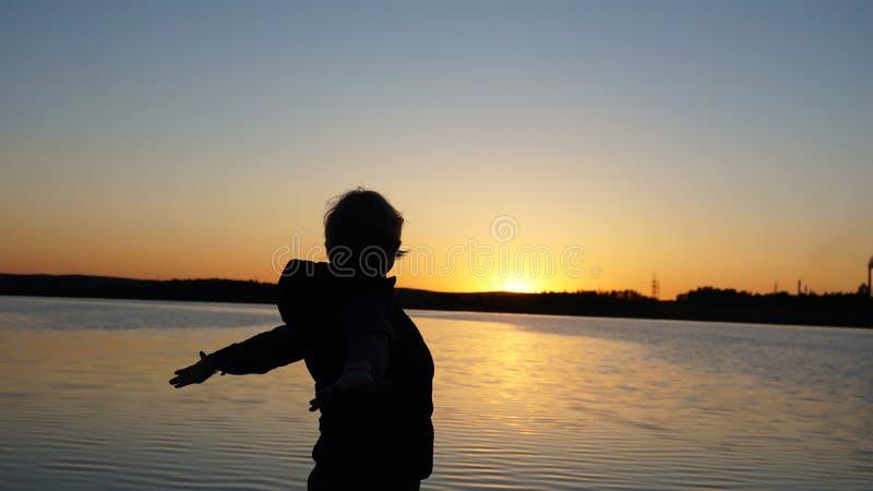 Schwarzes Schattenbild eines M?dchens gegen den Sonnenunterganghimmel lizenzfreies stockbild
