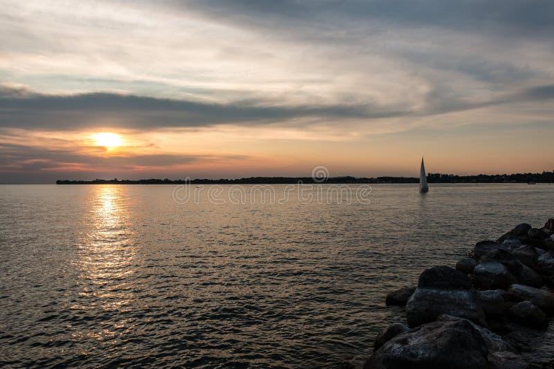 Schwarzes Segelboot und ein kleiner schwarzer Landsteg ins Wasser und ein goldener Sonnenuntergang stockfotos