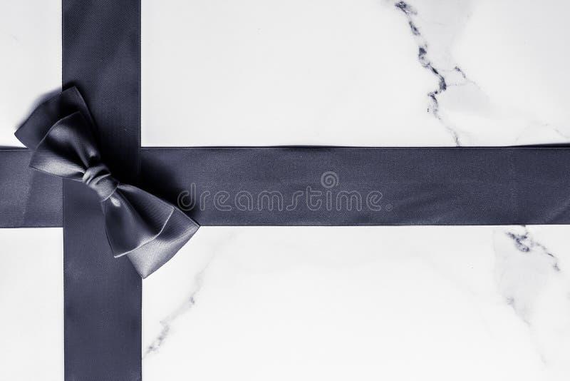 Schwarzes Seidenband und Bogen auf dem Marmorhintergrund, flatlay lizenzfreies stockbild