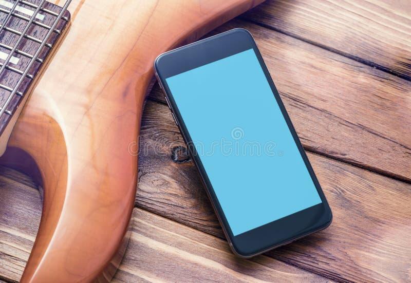 Schwarzes Smartphonemodell mit Gitarre lizenzfreies stockbild