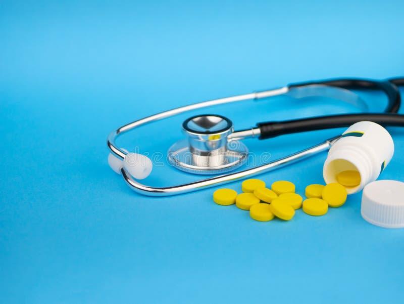 Schwarzes Stethoskop für Doktor und gelbe Pillen- und weiße Plastikflasche Pille im hand Blauer Hintergrund mit Kopienraum für lizenzfreie stockfotografie