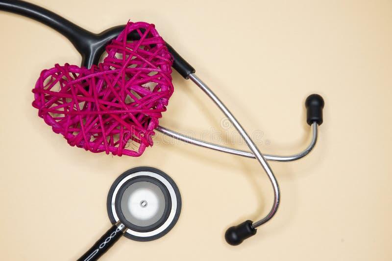 schwarzes Stethoskop und rotes Rattanherz lizenzfreie stockfotos