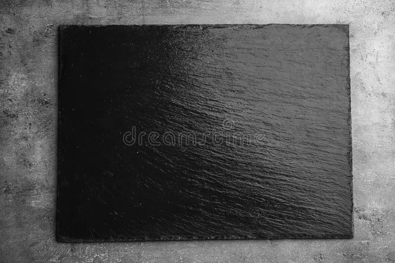 Schwarzes strukturiertes Schieferbrett auf dunklem Hintergrund stockfoto