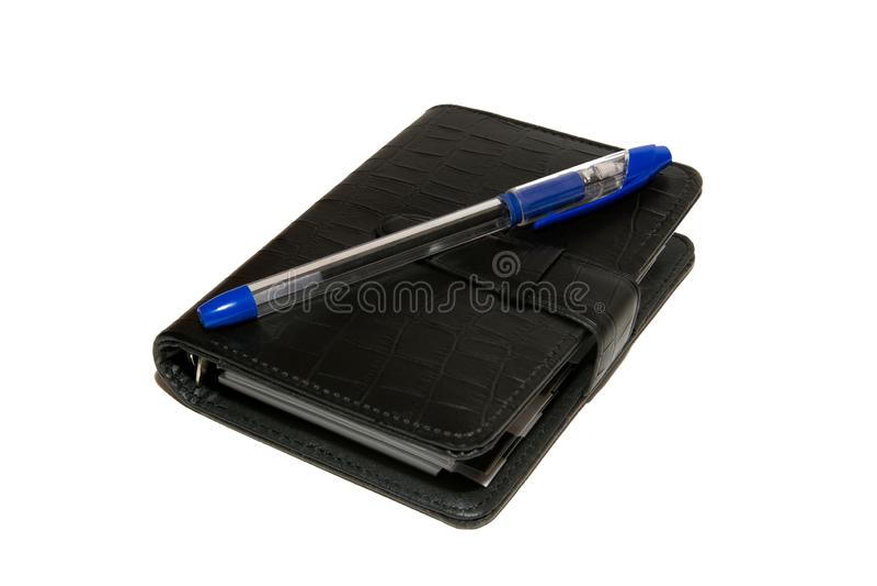 Schwarzes Tagebuch mit einem blauen Kugelschreiber liegt auf einer weißen Tabelle lizenzfreie stockfotos