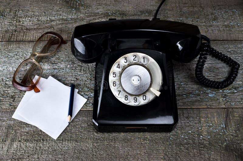 Schwarzes Telefon der Weinlese und alte Gläser stockfotografie