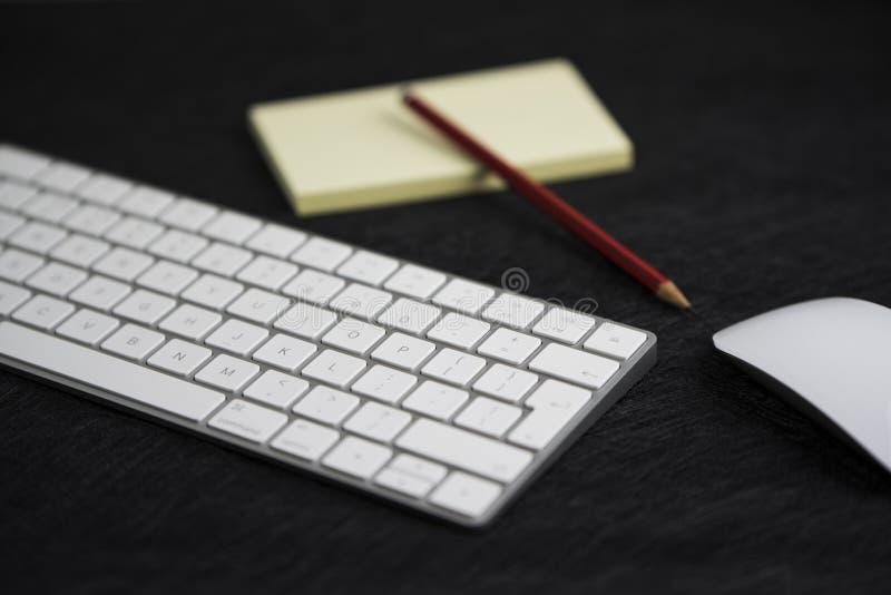 Schwarzes Texturbrett mit einem Bleistift auf einem Papier, einer Tastatur und einer Maus lizenzfreies stockfoto