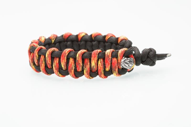 Schwarzes und orange umsponnenes Armband auf Weiß lizenzfreies stockbild