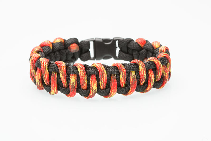 Schwarzes und orange umsponnenes Armband auf Weiß stockbild
