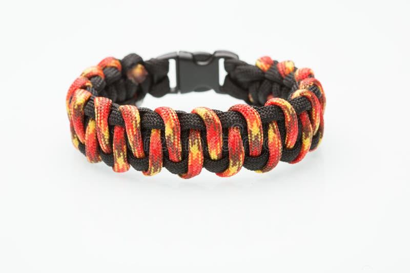 Schwarzes und orange umsponnenes Armband auf Weiß stockbilder