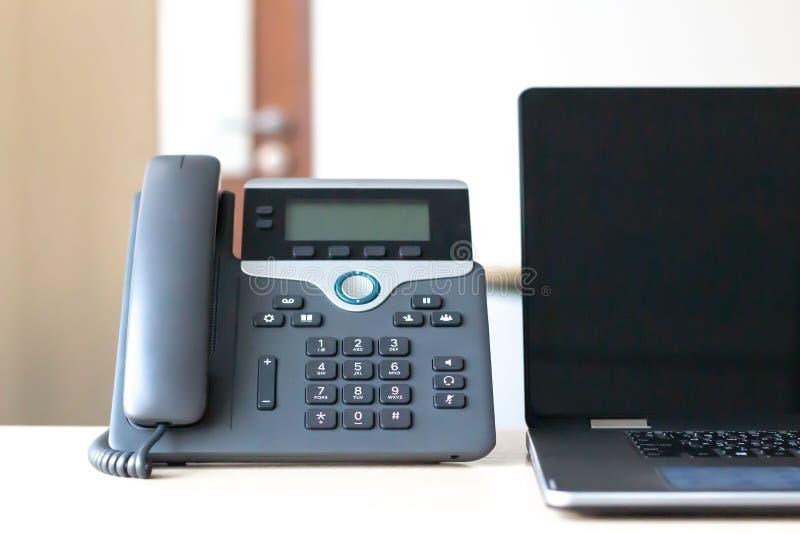 Schwarzes voip Telefon auf Schreibtisch lizenzfreies stockfoto