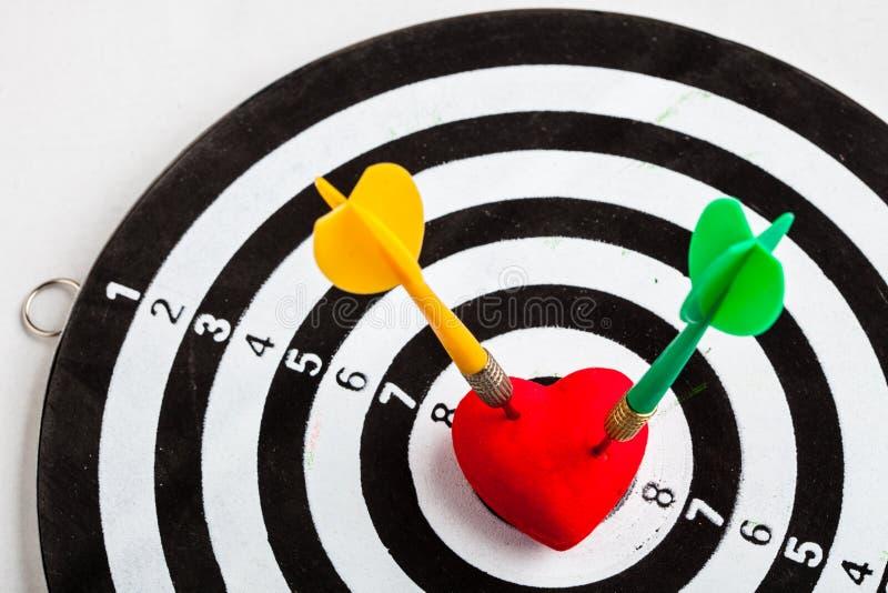 Schwarzes weißes Ziel mit zwei Pfeilen im Herzliebessymbol als Bullauge stockfoto