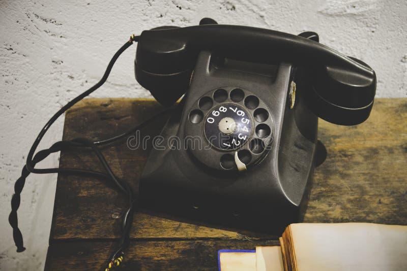 Schwarzes Weinlesetelefon auf Holztisch mit altem leerem Notizbuch und weißer Schmutzzementputzwand stockbild