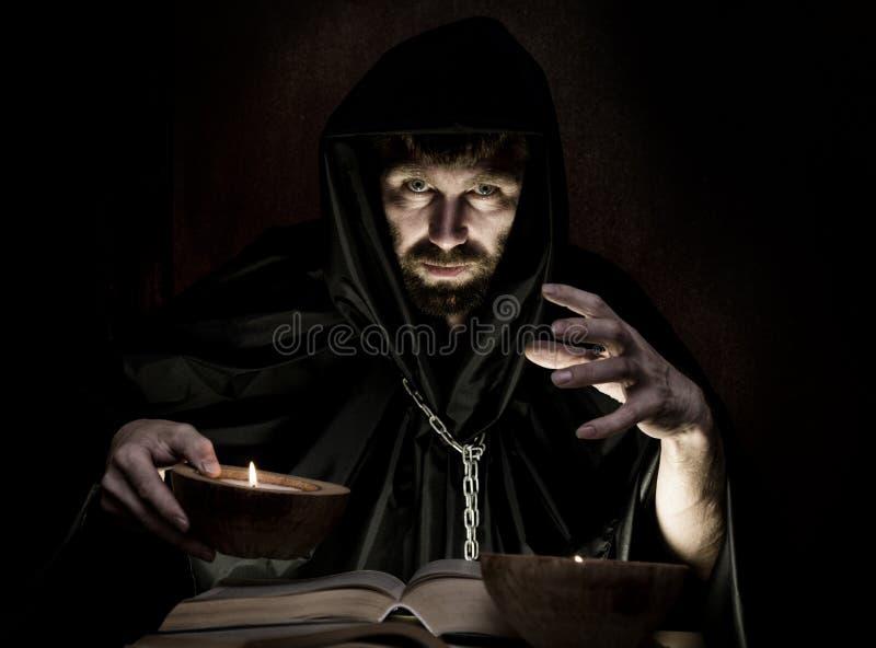Schwarzkünstler wirft Banne vom starken alten Buch durch Kerzenlicht auf einem dunklen Hintergrund lizenzfreies stockbild