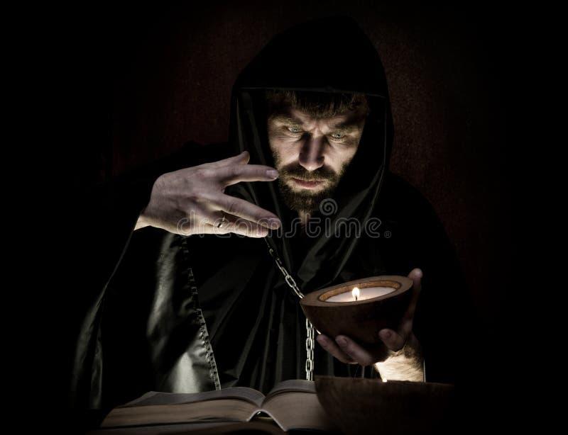 Schwarzkünstler wirft Banne vom starken alten Buch durch Kerzenlicht auf einem dunklen Hintergrund lizenzfreie stockfotos