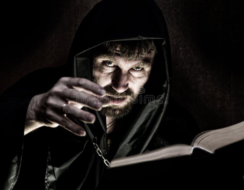 Schwarzkünstler wirft Banne vom starken alten Buch durch Kerzenlicht auf einem dunklen Hintergrund stockfotografie