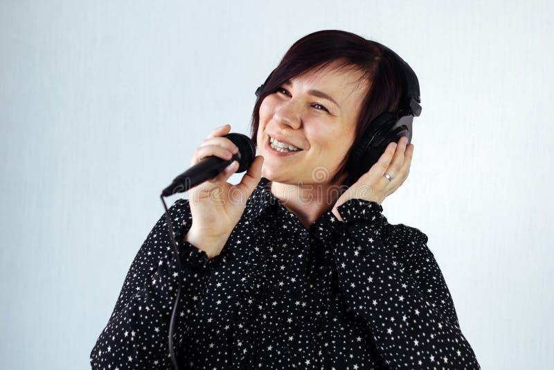 Schwarzkleid des kurzen Haares des Mädchens mit Kopfhörern und Mikrofon lizenzfreie stockfotografie