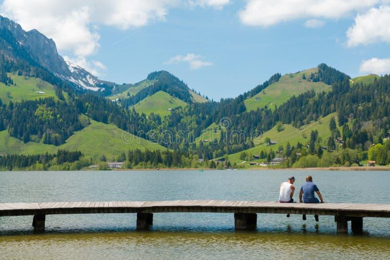 Schwarzsee, franco/Suiza - 1 de junio de 2019: dos mejores amigos de los hombres disfrutan de la opinión de la orilla del lago de imagen de archivo libre de regalías