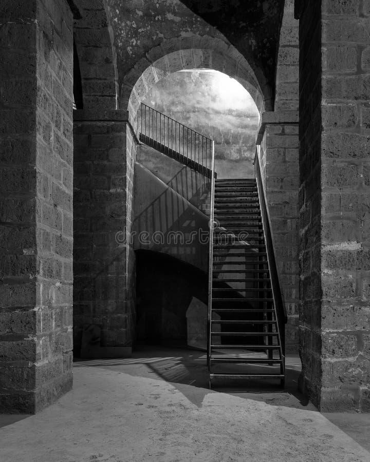 Schwarzweiß aus dunkel verlassener unterirdischer Durchgang mit Steinsteinsäulen und Metalltreppe stockbilder