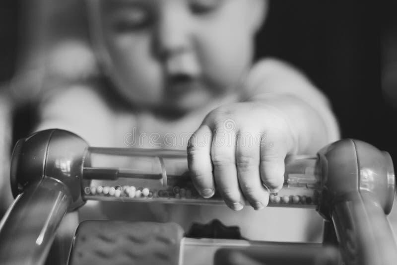 Schwarzweiss-Abschluss oben des Babys, das mit Spielzeug spielt lizenzfreies stockfoto