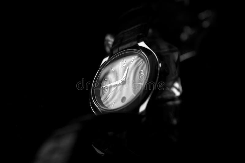 Schwarzweiss-Bild der Edelstahlarmbanduhr der eleganten Frauen mit einem schwarzen Lederband lizenzfreies stockbild
