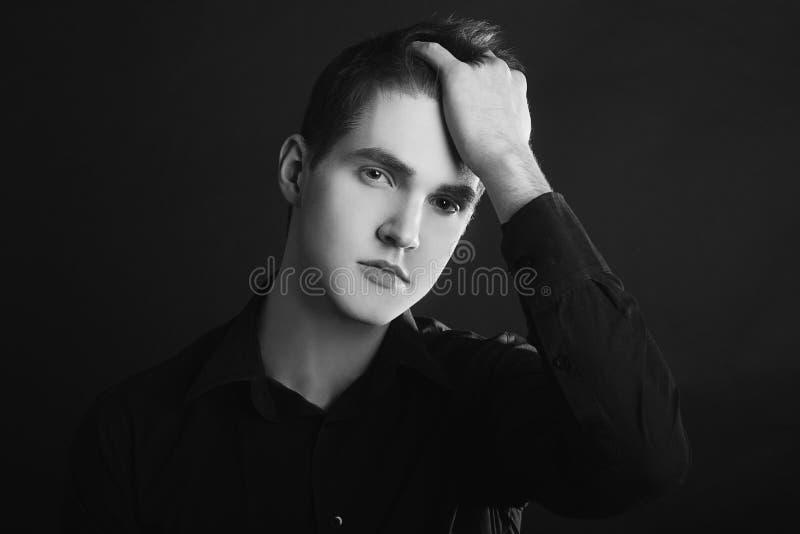 Schwarzweiss-Bild der einzelnen Stellung im jungen hübschen ernsten Mann des Profils über schwarzem Hintergrund mit Kopienraum lizenzfreie stockfotografie