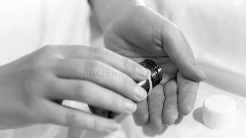 Schwarzweiss-Bild der Frau Flasche mit Pillen in der Hand halten stockbilder