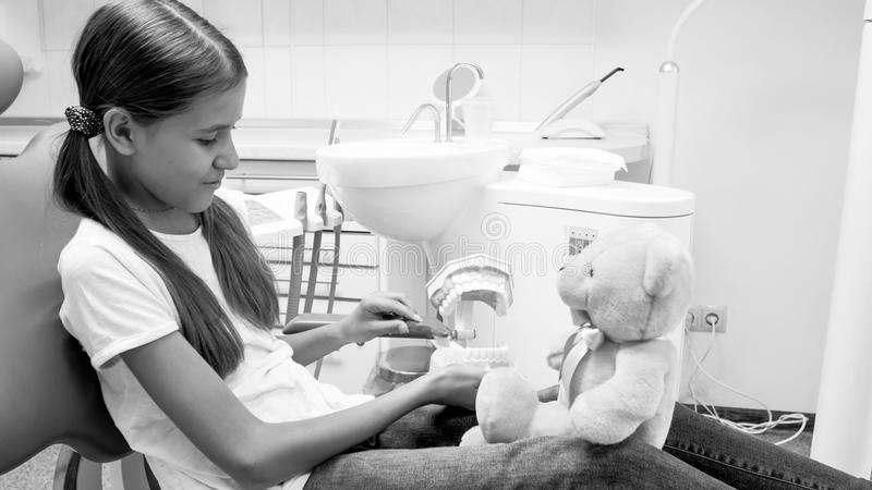 Schwarzweiss-Bild der Jugendlichen ihrem Teddybären beibringend, wie man richtig Zähne säubert lizenzfreies stockbild