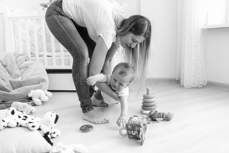 Schwarzweiss-Bild der jungen Mutter versuchend, sich ihr schreiendes Baby zu beruhigen stockbild