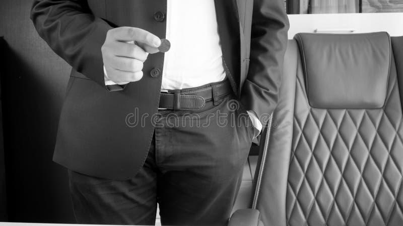 Schwarzweiss-Bild des Geschäftsmannes Münze in der Hand halten lizenzfreie stockbilder