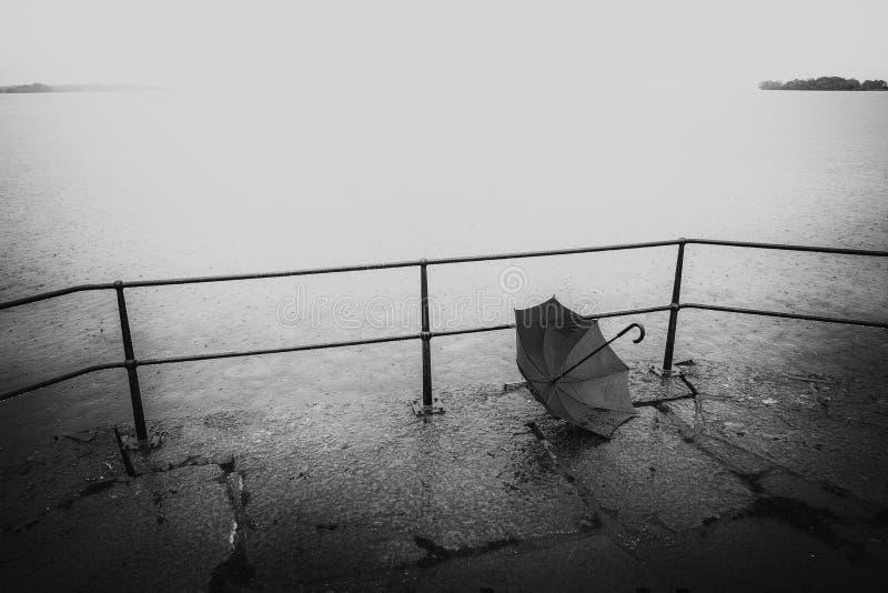 Schwarzweiss-Bild des vergessenen Regenschirmes ein regnerischen Tag durch das Wasser stockfotos