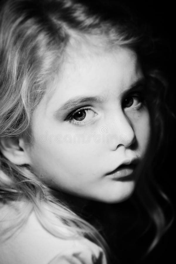 Schwarzweiss-Bild eines blonden kleinen Mädchens, das mich betrachtet lizenzfreies stockfoto