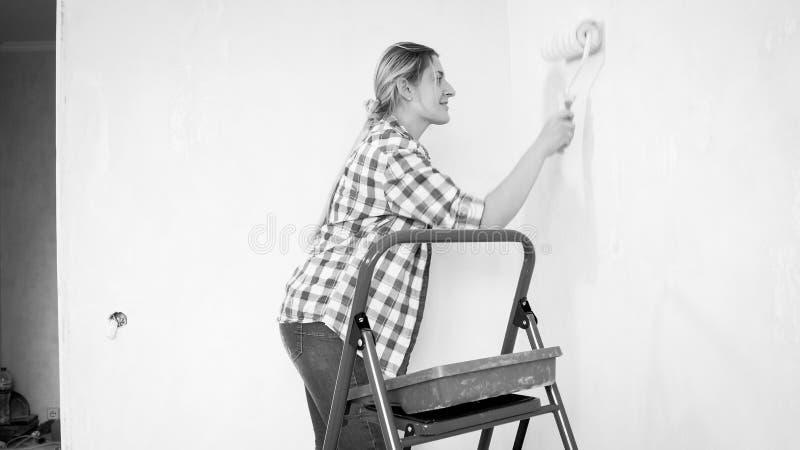 Schwarzweiss-Bild von schönen Malereiwänden der jungen Frau mit Farbenrolle lizenzfreie stockfotos