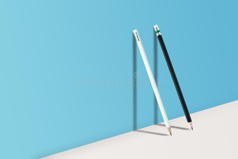 Schwarzweiss-Bleistifte, die auf weißem Boden und Schatten auf blauer Wand stehen lizenzfreies stockfoto