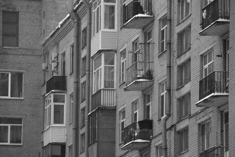 Schwarzweiss-Fenster und Balkone eines Backsteinhauses stockfotografie