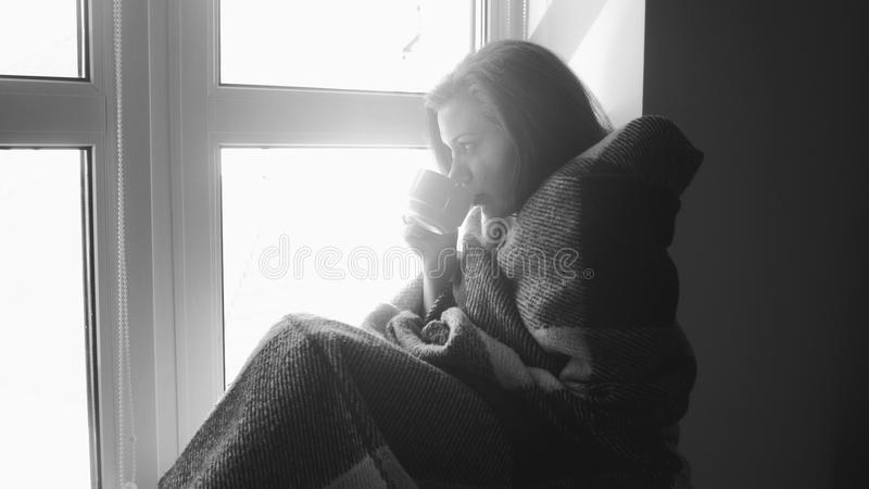 Schwarzweiss-Foto der jungen Frau in trinkendem Tee des Plaids am Fenster stockbilder