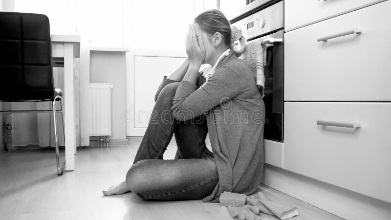 Schwarzweiss-Foto der jungen Hausfrau schreiend auf Boden am Wohnzimmer lizenzfreie stockfotos
