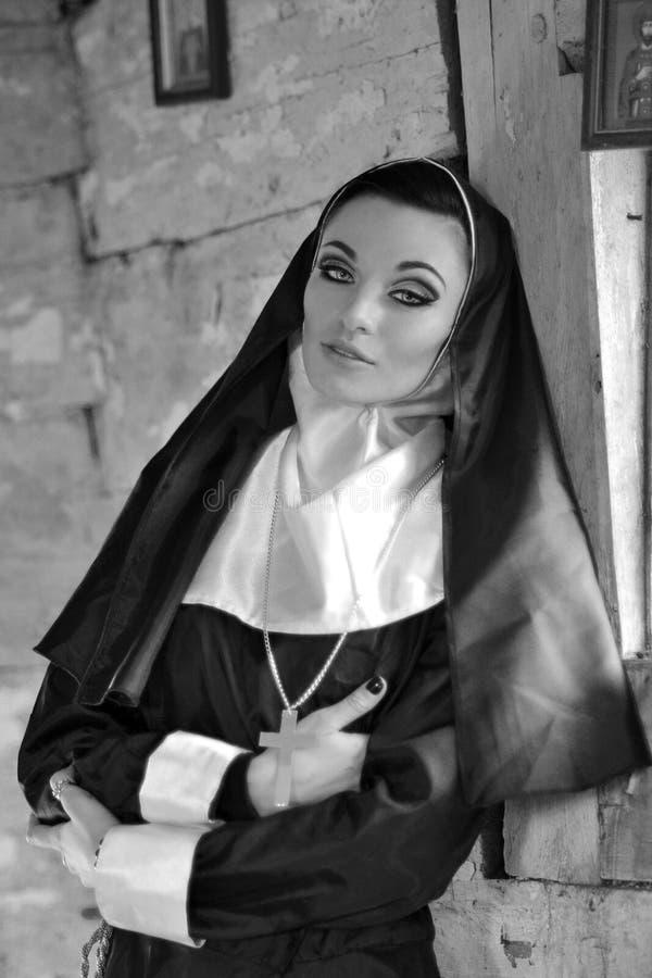 Schwarzweiss-Foto der religiösen schönen Nonne Betende Nonne in der Kirche Nahaufnahmehände von Nonnen, das gegen seinen Kasten S lizenzfreie stockfotos