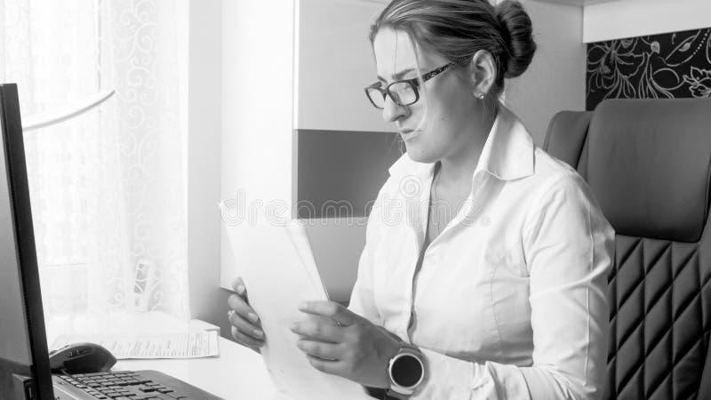 Schwarzweiss-Foto der schönen jungen Geschäftsfrau, die mit Dokumenten im Büro arbeitet stockfotografie