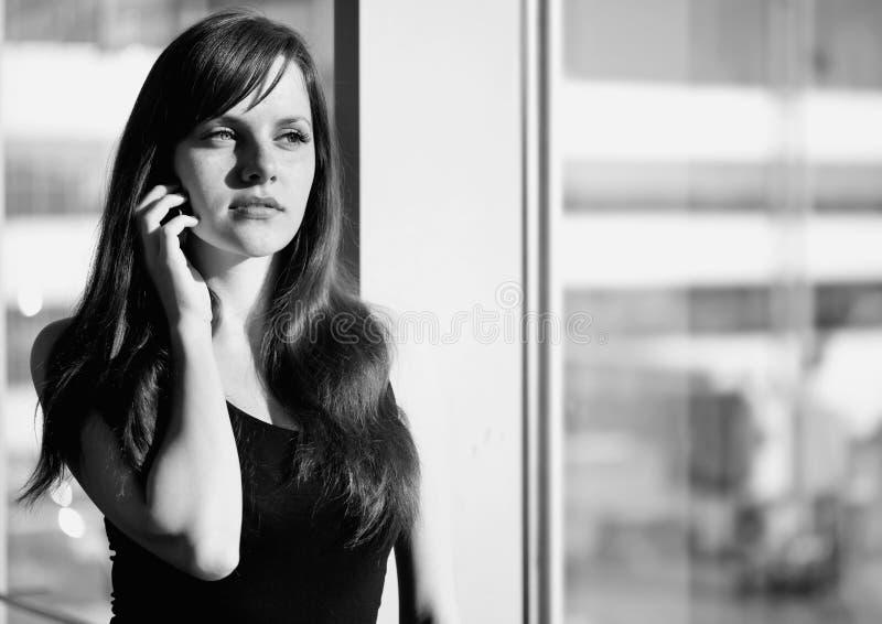 Schwarzweiss-Foto der Stellung der jungen Frau nahe dem Fenster im Flughafen stockfoto