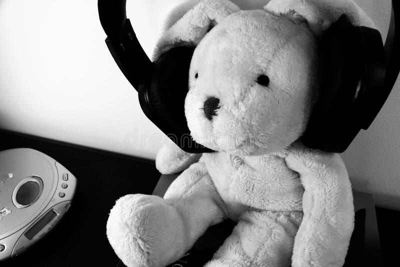 Schwarzweiss-Foto des angefüllten Plüschspielzeugs mit drahtlosen Kopfhörern und einem Portalcd-player stockbilder