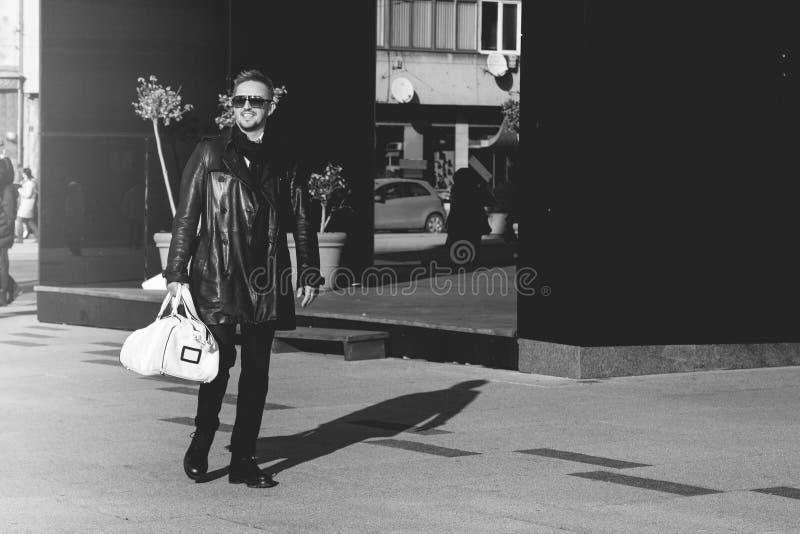 Schwarzweiss-Foto des beauy männlichen Modells beim Sonnenbrillegehen lizenzfreies stockbild