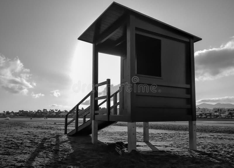 Schwarzweiss-Foto des Leibwächterhauses auf dem Sand an einem ruhigen Strand ohne Schutz oder Leute an der Sonnenuntergangstunde  lizenzfreie stockbilder