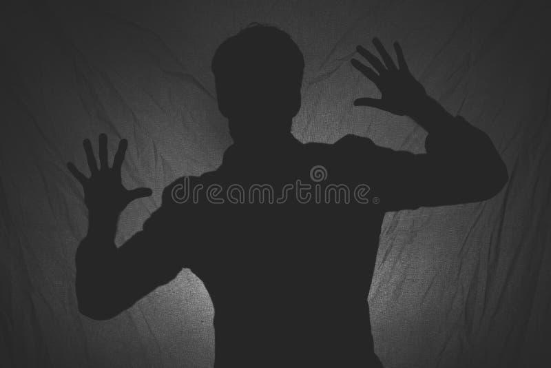 Schwarzweiss-Foto des Schattens eines Mannes hinter dem Gewebe lizenzfreies stockfoto