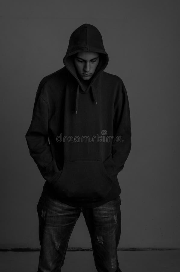 Schwarzweiss-Foto des upsed Jugendlichen mit dem Hoodie, der unten wieder schaut lizenzfreie stockbilder