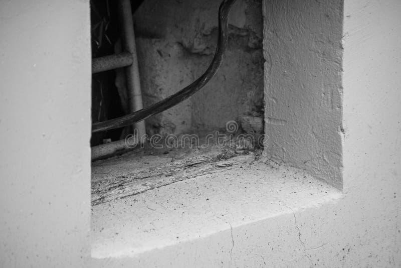 Schwarzweiss-Foto eines elektrischen Drahtes, der vom Keller eines Gebäudes kommt stockbild
