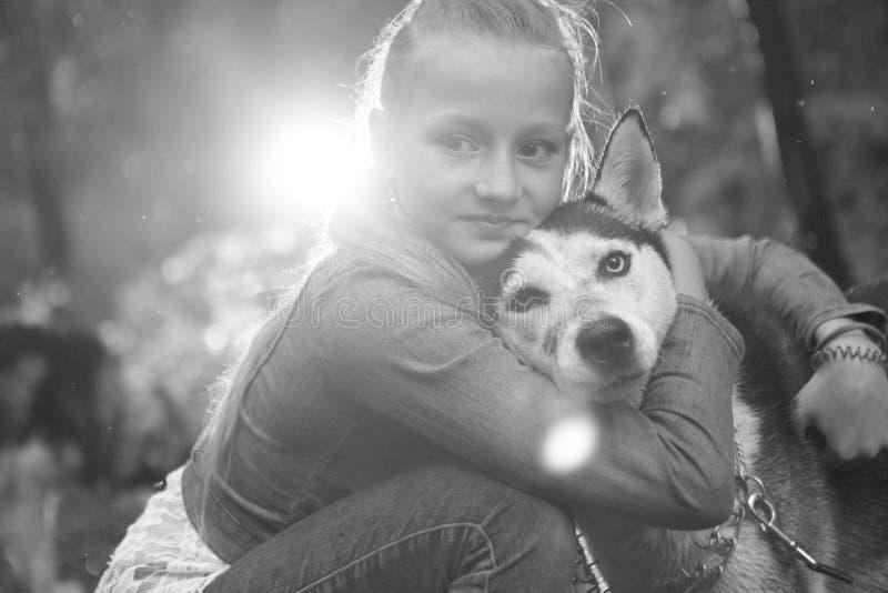 Schwarzweiss-Foto eines Mädchens, das ihren Hundeschlittenhund auf dem Hintergrund umarmt, verlässt im Frühjahr lizenzfreie stockbilder