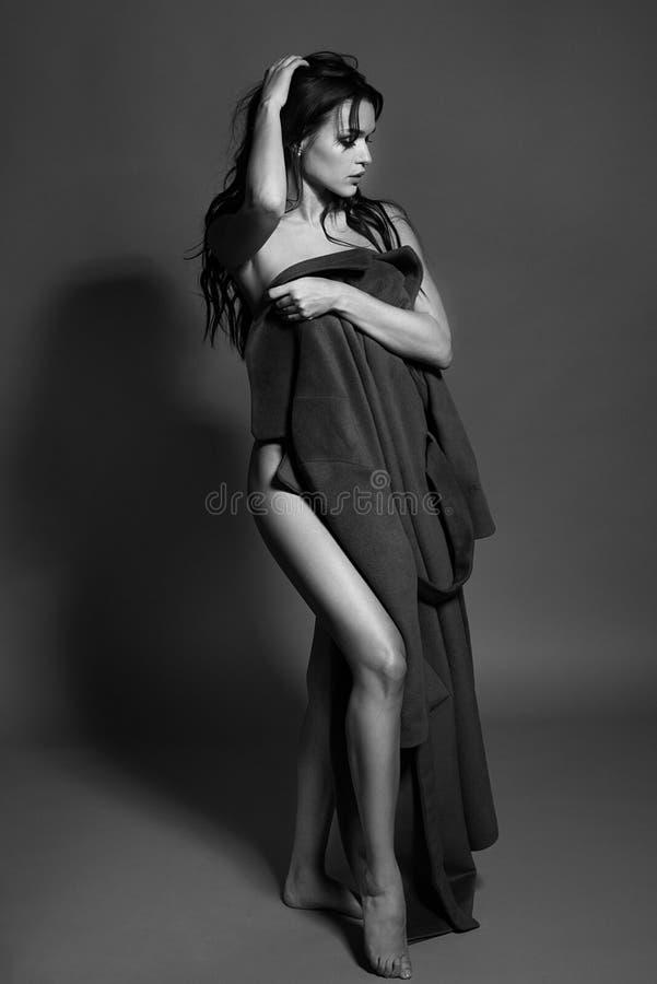 Schwarzweiss-Foto eines verlockenden Brunettemädchens im Studio Reizvolle toplesse Frau einfarbiges Bild lizenzfreie stockfotografie