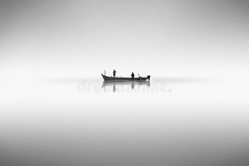 Schwarzweiss-Foto mit einem Boot auf dem Wasser im Nebel lizenzfreies stockfoto